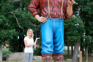 a woman standing next to a paul bunyan statue